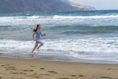 Fille dans le T-shirt rayé fonctionnant le long de la plage photographie stock