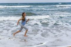 Fille dans le T-shirt rayé fonctionnant le long de la plage photographie stock libre de droits