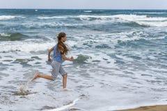 Fille dans le T-shirt rayé fonctionnant le long de la plage photo libre de droits