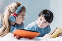 Fille dans les écouteurs et le garçon à l'aide des comprimés numériques tout en se trouvant sur le lit Photo stock