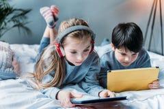 Fille dans les écouteurs et le garçon à l'aide des comprimés numériques tout en se trouvant sur le lit Image stock