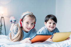 Fille dans les écouteurs et le petit garçon à l'aide des comprimés numériques tout en se trouvant Photographie stock