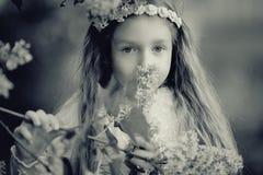 Fille dans les branches du lilas Images stock