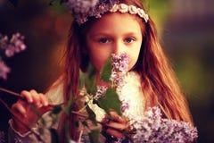 Fille dans les branches du lilas Photographie stock