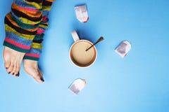 Fille dans les chaussettes et entourée par le café et le thé Le concept de l'arrêt pour des pauses-café boissons Photos libres de droits
