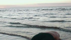 Fille dans les cheveux foncés de secousse de robe à l'eau sur la côte Photoshoot heureux modèle Mer clips vidéos