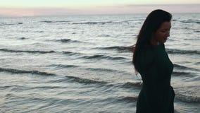 Fille dans les cheveux foncés de secousse de robe à l'eau sur la côte Photoshoot Mode modèle Mer banque de vidéos