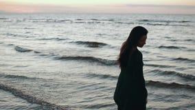 Fille dans les cheveux foncés de secousse de robe à l'eau sur la côte Photoshoot Sourire modèle Mer banque de vidéos