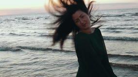 Fille dans les cheveux foncés de secousse de robe à l'eau sur la plage Photoshoot Regardez in camera Mer banque de vidéos