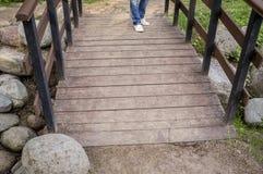 Fille dans les espadrilles blanches et des jeans se tenant sur un pont en bois, wh Photographie stock libre de droits