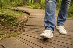 Fille dans les espadrilles et des jeans marchant le long du chemin en bois écologique Image libre de droits