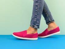 Fille dans les espadrilles rouges et des jeans déchirés marchant sur le plancher bleu Photo stock