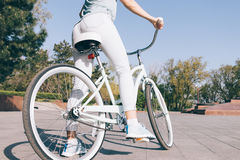 Fille dans les jeans et le T-shirt se reposant sur une bicyclette bleue de vintage dans p Photos stock
