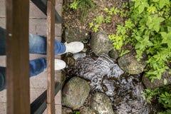 Fille dans les pantoufles et des jeans se tenant sur un pont en bois, qui est Images libres de droits