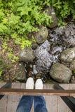 Fille dans les pantoufles et des jeans se tenant sur un pont en bois, qui est Photographie stock
