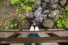 Fille dans les pantoufles et des jeans se tenant sur un pont en bois, qui est Photo stock