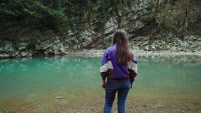 Fille dans les supports de style occasionnel sur le rivage d'un lac bleu propre dans les montagnes, bourdonnant banque de vidéos