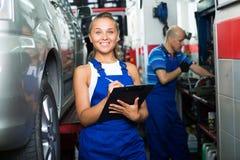 Fille dans les vêtements de travail dans l'atelier de mécanicien automobile photo libre de droits