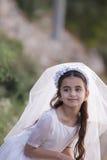 Fille dans sa premiers robe et voile de communion images stock