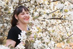 Fille dans un arbre de fleur de jour ensoleillé d'été Photo stock