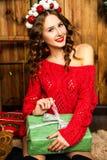 Fille dans un cadeau rouge de Noël d'ouverture de chandail Concept d'an neuf Photographie stock libre de droits