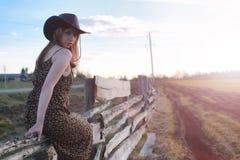 Fille dans un chapeau de cowboy à la barrière images stock