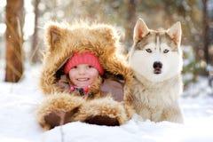 Fille dans un chapeau de fourrure se trouvant à côté du chien de traîneau dans la neige dans la forêt Photos libres de droits