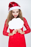 Fille dans un chapeau de Noël tenant des bannières sous forme de nuages Photo stock