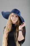 Fille dans un chapeau et une robe noire Photos stock