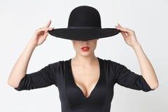 Fille dans un chapeau noir Image stock