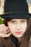 Fille dans un chapeau noir. Plan rapproché Photo libre de droits