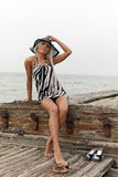 Fille dans un chapeau se reposant sur un bateau cassé Photographie stock