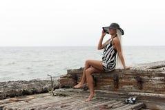 Fille dans un chapeau se reposant sur un bateau cassé Image libre de droits