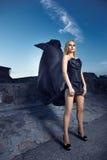 Fille dans un corset avec un long train au mur Photo libre de droits