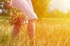 Fille dans un domaine avec un groupe de fleurs sauvages dans leurs mains Le concept de la pureté et unité avec la nature, lumière Photographie stock
