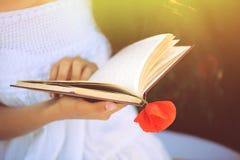 Fille dans un domaine de pavot avec un livre images libres de droits