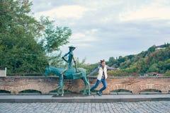 Fille dans un gilet blanc avec un sac à dos Prochain âne en bronze avec un cohete de touristes de Sighnaghi Photo libre de droits