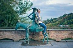 Fille dans un gilet blanc avec un sac à dos Prochain âne en bronze avec un cohete de touristes de Sighnaghi Images stock