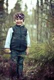 Fille dans un gilet souriant dans une forêt Photos stock