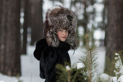 Fille dans un jour givré d'hiver de chapeau de fourrure marchant dans les bois Image stock