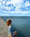 Fille dans un maillot de bain et un cap, sur la plage contre le beau ciel illustration stock