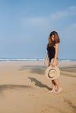 Fille dans un maillot de bain et un chapeau noirs marchant sur la plage Image libre de droits