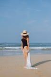 Fille dans un maillot de bain et un chapeau noirs marchant sur la plage Photographie stock