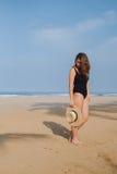 Fille dans un maillot de bain et un chapeau noirs marchant sur la plage Photo stock