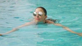 Fille dans un maillot de bain noir et des lunettes de soleil banque de vidéos