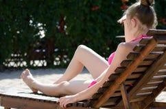 Fille dans un maillot de bain sur une chaise longue dans l'arrière-cour Image libre de droits
