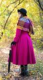 Fille dans un manteau cramoisi lumineux marchant dans le jour ensoleillé d'automne de forêt images stock