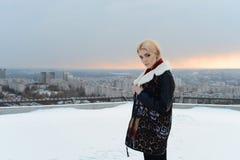 Fille dans un manteau de peau de mouton brun posant près d'un lac congelé Images libres de droits
