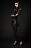 Fille dans un manteau noir en cuir, le pantalon et des chaussures, se tenant sur un bla Photo stock