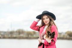 Fille dans un manteau rose et un chapeau noir avec un petit chien Image stock